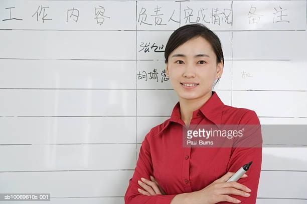 Businesswoman standing by flip chart, smiling, portrait