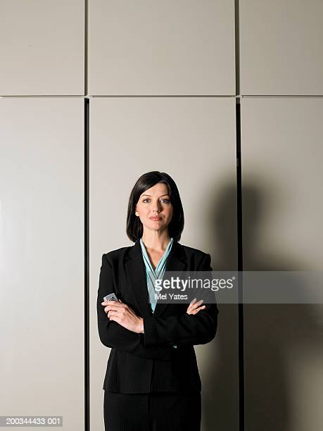Businesswoman standing by wall, arms folded, portrait