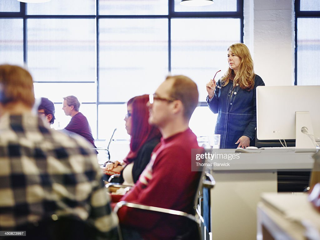 Businesswoman standing during meeting in office : Stock Photo