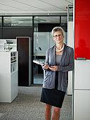 Businesswoman standing holding folders in office