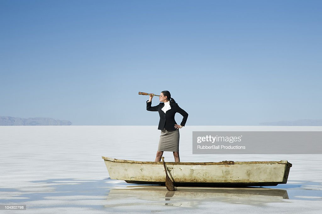 businesswoman standing in a row boat in the middle of nowhere holding a telescope