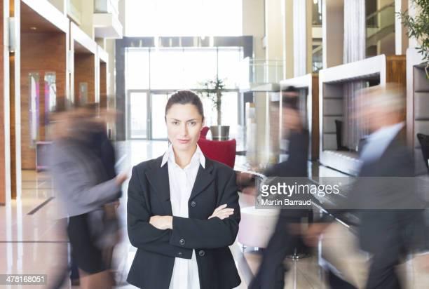 Femme d'affaires debout dans l'effervescence du hall