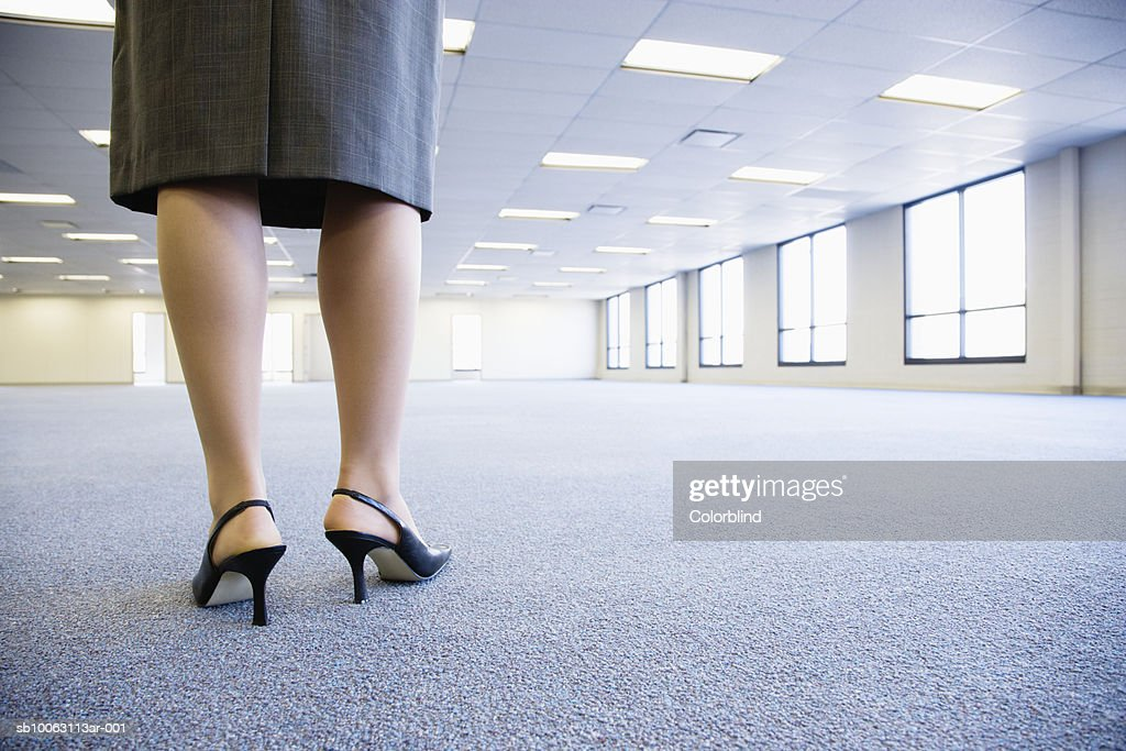 Businesswoman standing in empty office, low section : Stock Photo