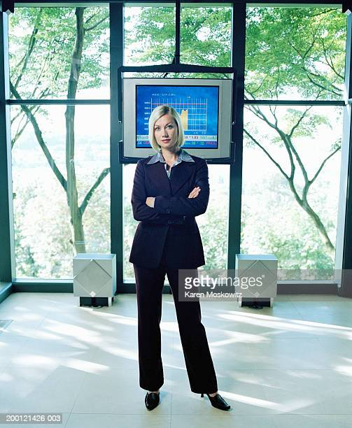 Businesswoman standing in front of graph on tv monitor, arms crossed