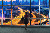 Businesswoman standing in office and looking in city. Business Concept