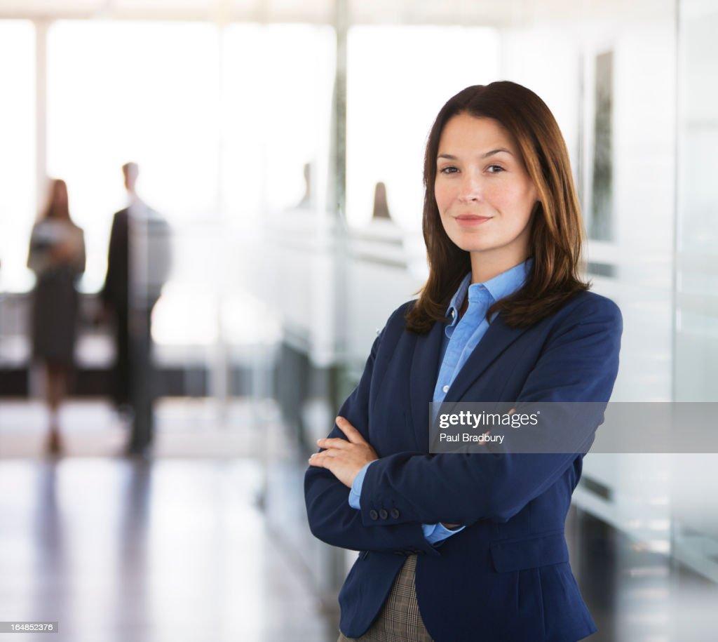 Businesswoman standing in office hallway
