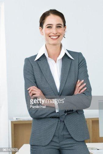 Businesswoman standing in office, smiling : Bildbanksbilder