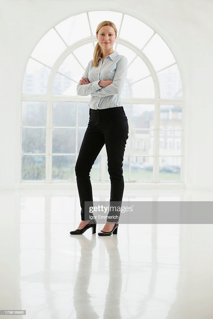 Businesswoman standing in sparse white room