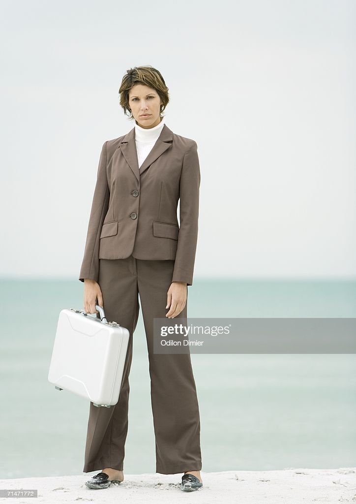 Businesswoman standing on beach holding briefcase : Stock Photo