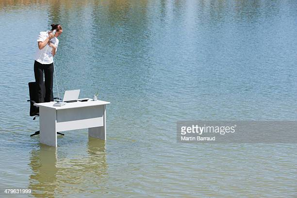 Businesswoman standing on chair at desk in water with phone