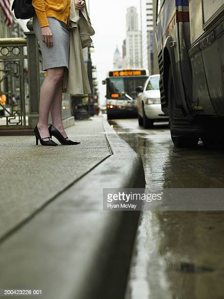 Businesswoman  standing on curb, low angle view
