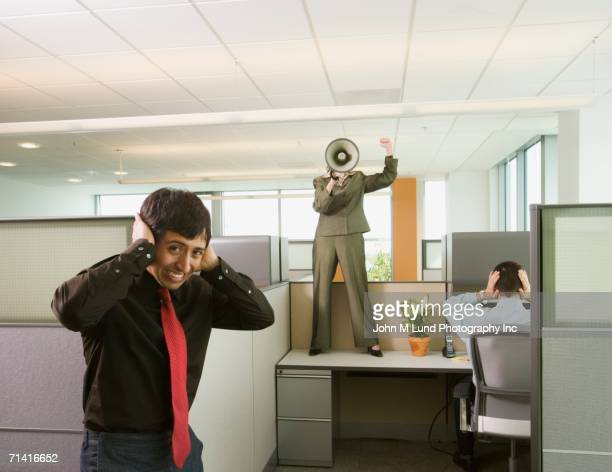 Businesswoman standing on desk yelling into megaphone