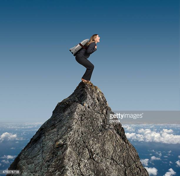 Businesswoman standing on mountaintop with rocket strapped to her back