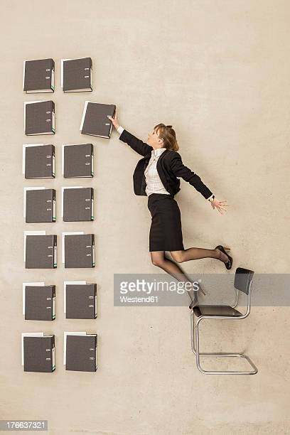 Businesswoman standing on office chair arranging files