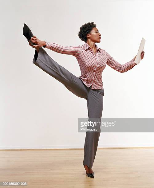 Businesswoman standing on one leg, looking at document