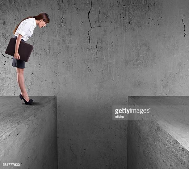 Femme d'affaires debout sur le bord d'un mur et en duvet