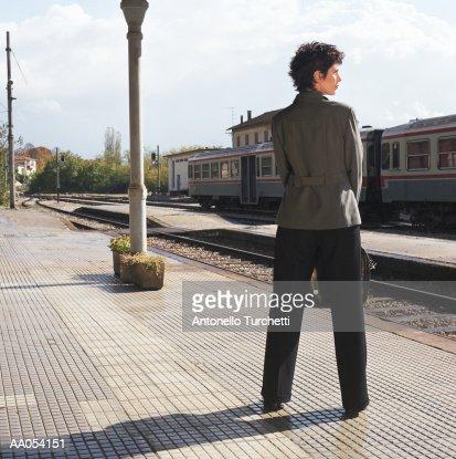 Businesswoman standing on train platform, rear view