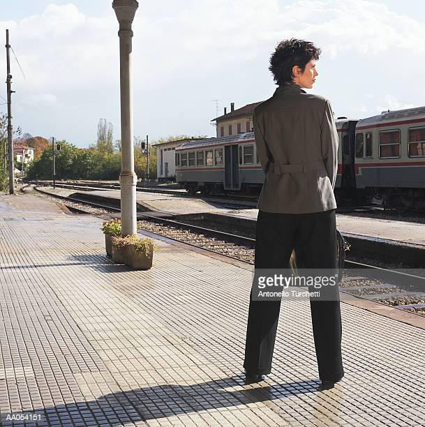 Businesswoman standing on train platform, rear view