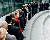 Businesswoman Standing Out in a Line of Business People Waiting Outdoors on a Step