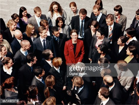 Businesswoman Standing Outdoors Surrounded by a Large Group of Business People : Stock Photo