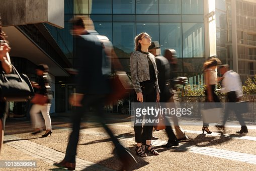 Businesswoman standing still on a busy street : Stock Photo