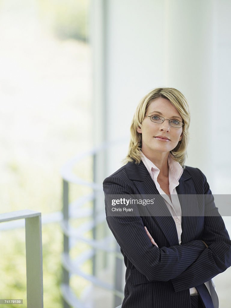 Businesswoman standing with arms crossed : Stock Photo