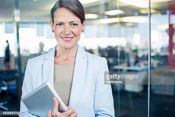 Businesswoman standing with digital tablet