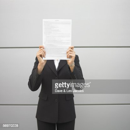 Businesswoman standing with document in front of face : Stock Photo