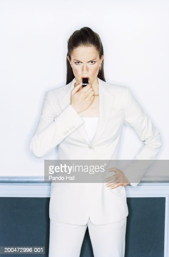 Businesswoman standing with hand on hip blowing whistle, portrait