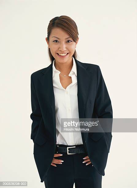 Businesswoman standing with hand on hips, smiling, portrait