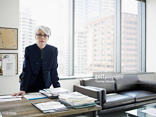 Businesswoman standing with hands resting on desk
