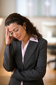 Businesswoman standing with headache