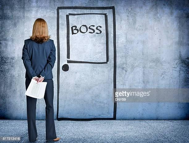 Businesswoman Standing With Report In Front Of Boss' Door