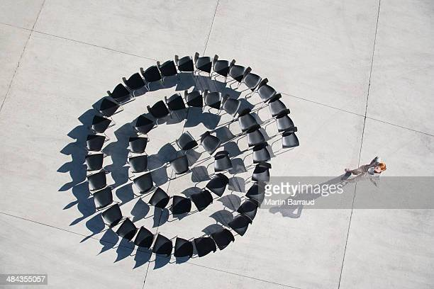 Businesswoman standing with spiral of office chairs