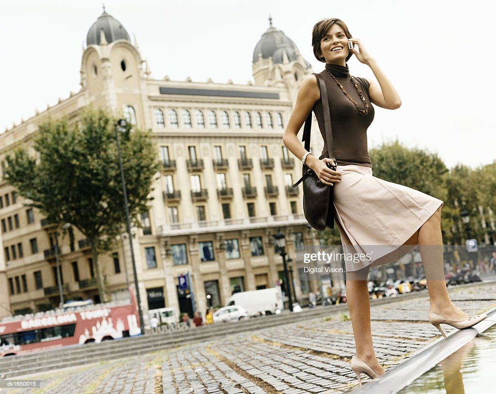 Businesswoman Stands in the Street Talking on Her Mobile Phone, Building Exterior in the Background, Barcelona, Spain : Stock Photo
