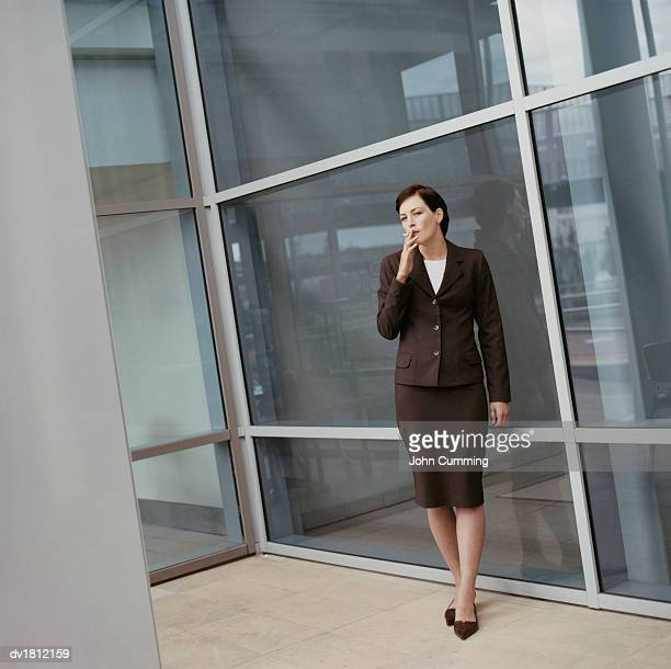 Businesswoman Stands Outside a Glass Building Having a Cigarette Break