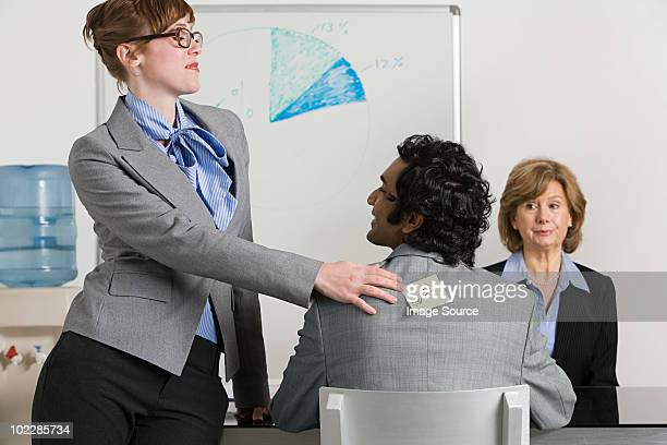 Businesswoman sticking adhesive note to man's back
