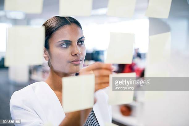 Businesswoman sticking notes on to window, business planning