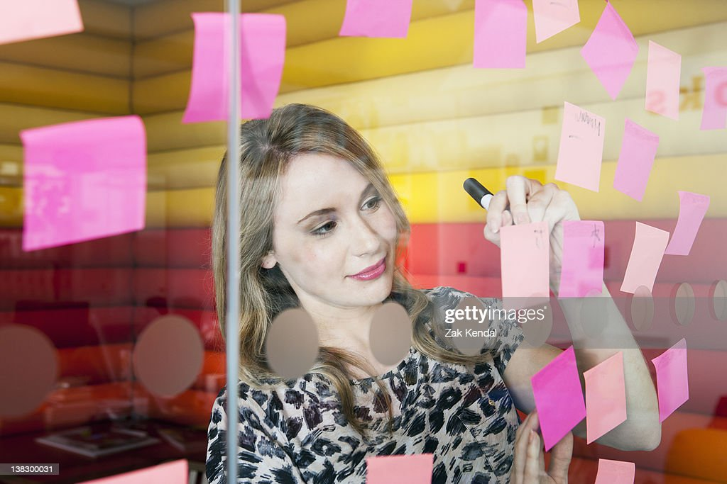 Businesswoman sticking notes on window : Stock Photo