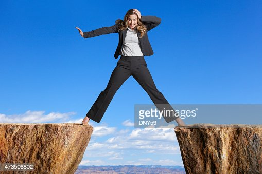 Businesswoman straddling the divide created by two cliffs