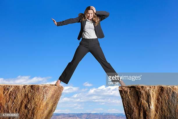 Geschäftsfrau entlang des divide von zwei Klippen