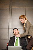Businesswoman strangling businessman