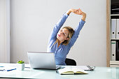Young Businesswoman Stretching Her Arms With Laptop On Desk