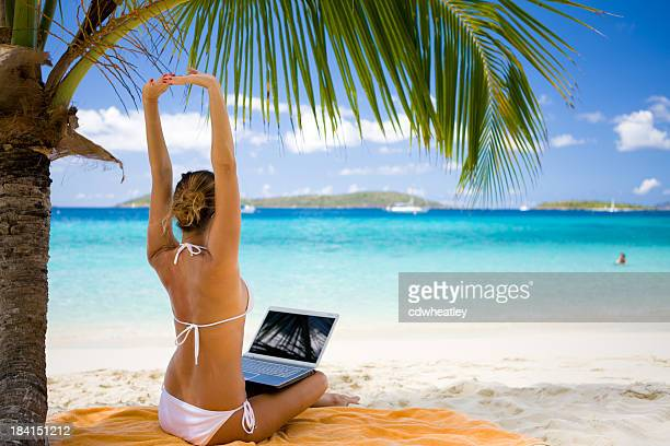 businesswoman stretching while working on laptop at the Caribbean beach