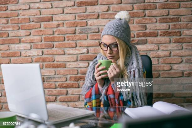 Businesswoman suffering with flu having hot drink at work