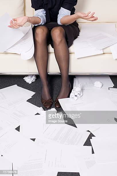 Geschäftsfrau umgeben von Papier
