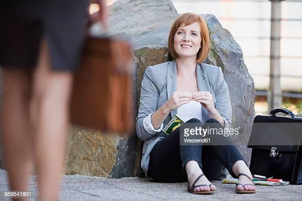 Businesswoman taking a break, sitting on ground rolling cigarette