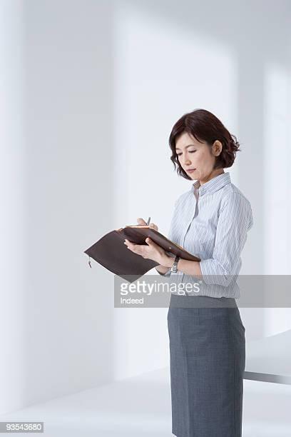 Businesswoman taking a diary