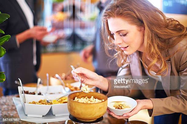 Businesswoman taking cashews from breakfast buffet