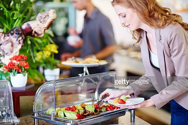 Businesswoman taking fruit from salad bar
